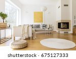 Small photo of Spacious white and wooden living room with modern fireplace and sofa