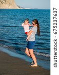 Small photo of Happy mother with a small girl walking on a beach. Zakynthos, Greece. Ionic Sea