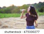 beautiful teenage girl blowing... | Shutterstock . vector #675330277