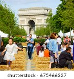 Small photo of PARIS, FRANCE - JUNE 4, 2017 - Children play and adults relaxing at BiodiversiTerre event (created by Gad Weil) showing relationship of man and nature in today's society. Triumph Arch at background.