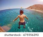 boy jumping from a wooden pier... | Shutterstock . vector #675556393