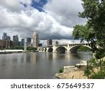 Small photo of Beautiful establishing shot view of Minneapolis skyline on summer day past the Stone Arch bridge overlooking Mississippi River