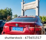 Small photo of Suzhou, China - Nov 5, 2016: Late model BMW X6 parked in front of the stone gate in classical Chinese design named Wumen Impression (Chinese characters). In a public park, along the Waicheng River.