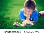 boy reading book  lying down on ... | Shutterstock . vector #676170793