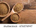 coriander seeds on a wooden... | Shutterstock . vector #676376947