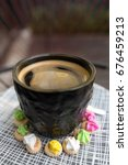 Small photo of Hot Americano coffee with crema top in a classy black glass surrounded buy colourful classic Ice Gem sweets biscuits on a patterned plate.