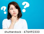 young woman with question marks. | Shutterstock . vector #676492333