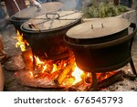 three pots are cooking outdoors ... | Shutterstock . vector #676545793