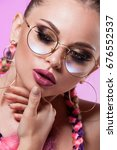 Small photo of Beautiful portrait of a young girl. Professional make-up and hairstyle made of colored plaits. Glamor shot on a pink background. Brady and rose-colored glasses.