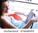 woman sitting at window reading | Shutterstock . vector #676668493