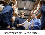 manager and workers in warehouse | Shutterstock . vector #676670533