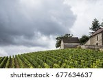 Small photo of MOREY-SAINT-DENIS, FRANCE - JUNE 29, 2017: View along stone wall, or clos, and with vineyards towards sign for the Grand Cru Appellation d'Origine Controlee Clos des Lambrays in Burgundy.