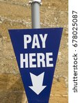 Small photo of Pay Here Sign against Stone Wall