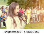 Small photo of NABEREZHNYE CHELNY, RUSSIA - July 9, 2017: Little girl sings a song in front of an audience on a local holiday