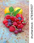 Small photo of Ripe raspberry, black currant, red currant, plums with a leaf on an old background