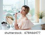 young woman is applying  makeup ...   Shutterstock . vector #678466477
