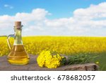 Small photo of rapeseed oil (canola) on background field and sky