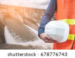 The abstract image of the engineer holding helmet and the hydroelectric dam is backdrop. the concept of clean energy, hydroelectricity, water management and engineering.