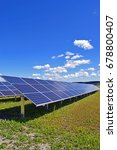 Small photo of Solar panels on field. Clear sky with a few small clouds on background. Vertical image.