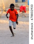 Small photo of FERLO DESERT, SENEGAL - APR 25, 2017: Unidentified Fulani little boy in red shirt runs along the street. Fulanis (Peul) are the largest tribe in West African savannahs