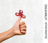 Small photo of Fidget spinner. Red hand spinner, fidgeting hand toy rotating on child's hand. Stress relief. Anti stress and relaxation adhd attention fad boy concept.