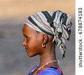 Small photo of FERLO DESERT, SENEGAL - APR 25, 2017: Unidentified Fulani girl in colored clothes and headscarf looks ahead. Fulanis (Peul) are the largest tribe in West African savannahs