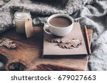 cup of coffee and candle on... | Shutterstock . vector #679027663