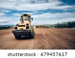 Small photo of Vibratory Soil Compactor during highway building. Industrial roadworks with heavy-duty machinery