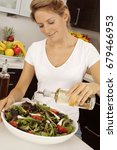 woman in kitchen pouring salad... | Shutterstock . vector #679466953
