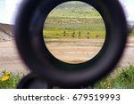 Small photo of A look through an optical sight aimed at a group of potential targets at the range, outdoor shot, Israeli army IDF training zone