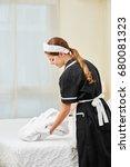 Small photo of Maid bringing fresh bathrobe in hotel room during housekeeping