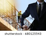 Small photo of Double exposure of Businessman holding construction helmet,Building and Construction background,Images used in the accompanying article.