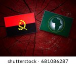 Small photo of Angolan flag with African Union flag on a tree stump isolated