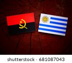 Small photo of Angolan flag with Uruguaian flag on a tree stump isolated
