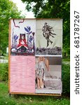 Small photo of Wooden board with different acts posters on green grass on July 2017 in Poznan, Poland