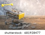 Small photo of coin in shopping cart on wooden in concept pay spend saving money, supermarket store