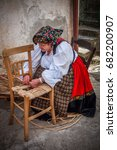 Small photo of Old woman tears the chassis of a chair