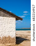Small photo of Traditional adobe house next to the sea under blue sky