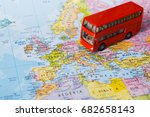 Small photo of Travelling abroad by bus concept. Red doubbledecker on the map, group tour to europe. Tourism and vacation background, closeup