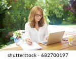 shot of a happy woman sitting... | Shutterstock . vector #682700197
