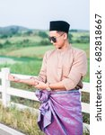 Small photo of Muadzam Shah, Malaysia - July 21st, 2017 : Young stylish handsome man is posing near white fence in a Malay traditional Malay clothing at First Dairy Farm , Malaysia.