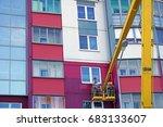 man paints a house on a crane