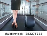 Small photo of Charming lady is on moving walkway at air terminal