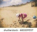 toddler girl picking up a shell ... | Shutterstock . vector #683339557