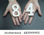 Small photo of On a black background, female hand with numbers eighty-four.