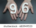 Small photo of On a black background, female hand with numbers ninety-six.