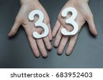 Small photo of On a black background, female hand with the number thirty-three.