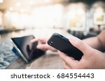 a hand holding a smartphone and ... | Shutterstock . vector #684554443