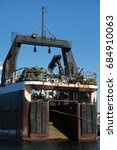 Small photo of Rear stern perspective of back ramp worn paint and old rusted industrial company commercial marine fishing vessel factory ship with overhead pulley crane and pile of dirty trawler drag nets on deck