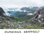 Young man in backward ball-cap and red rain jacket stands overlooking a huge glacial valley in the Talkeetna Range with clouds lining it